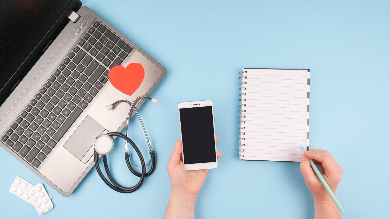 ordinateur, téléphone mobile, stéthoscope et calepin posés sur une table